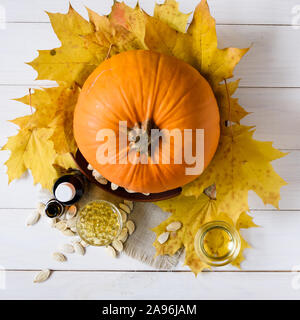 top wier, glass bottles and capsules with pumpkin oil on a pumpkin background on a white wooden table - Stock Photo
