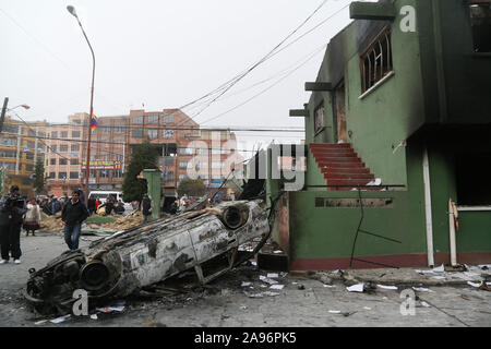 La Paz, Bolivia. 12th Nov, 2019. People pass a burnt out and knocked over car next to a destroyed police station. After the resignation of Bolivian President Morales, marauding gangs in the South American country are up to no good - now the military want to put an end to the spook. Credit: Gaston Brito/dpa/Alamy Live News - Stock Photo