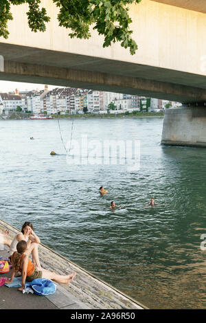 People floating in Rhine river in Basel - Stock Photo