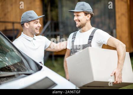 Portrait of a two delivery men in uniform standing together with check list and cardboard boxes near the cargo van vehicle outdoors - Stock Photo