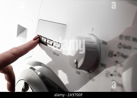 Closeup detail of woman's index finger with nail polish pushing button on white modern washing machine - Stock Photo