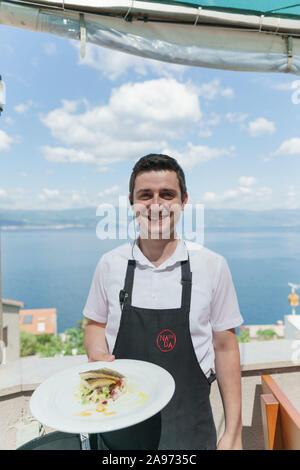 Waiter with a plate, Konoba Nada, on Krk island, Croatia - Stock Photo