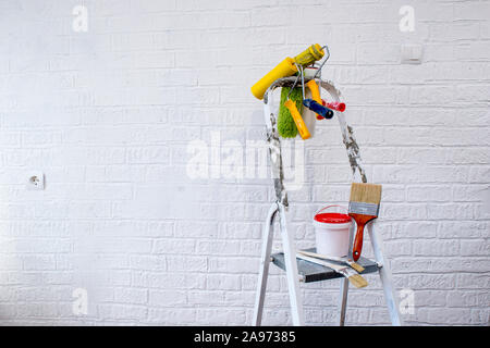 Painted metal stepladder with a bucket of paint, a set of colorful rollers and brushes on the background of a white wall decorated with bricks. - Stock Photo