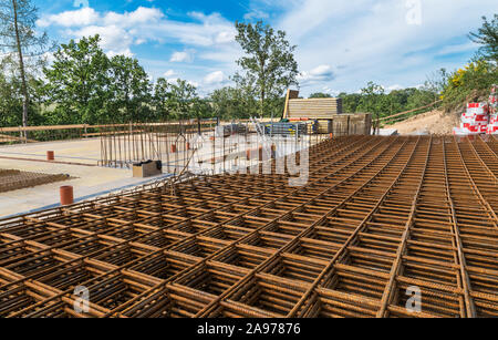 Reinforcing bars grid for ferroconcrete. Building foundations in green trees. Rebar mesh of rust brown steel wires for reinforced concrete and masonry. - Stock Photo