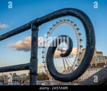 The Coca-cola London eye. The London eye with spiral handrail. Fantastic view, colorful autumn trees and blue sky with clouds. - Stock Photo