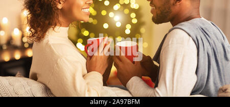 Couple enjoying hot coffee on Christmas eve, talking to each other against xmas tree - Stock Photo
