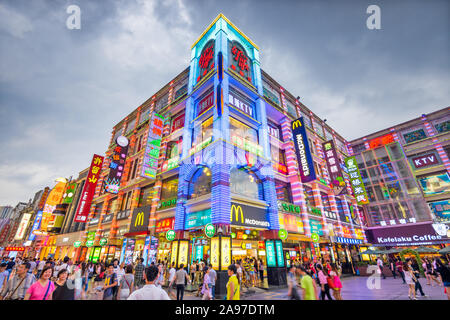 GUANGZHOU, CHINA - MAY 25, 2014: Pedestrians pass through Shangxiajiu Pedestrian Street. The street is the main shopping district of the city and a ma - Stock Photo