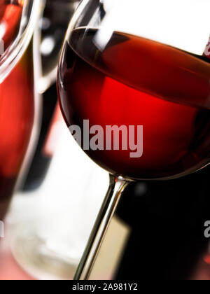 Red wine glass and bottles against white background - Stock Photo