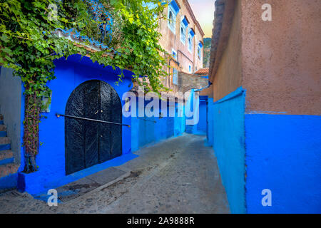 Narrow street with blue painted walls in old medina of Chefchaouen. Morocco, North Africa - Stock Photo