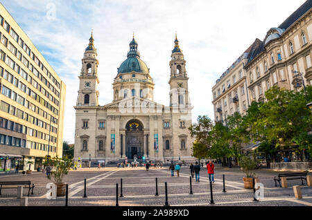 Budapest, Hungary - Nov 6, 2019: St. Stephen's Basilica and adjacent square with people. Roman Catholic basilica, a sample of neoclassical architecture. Ugly socialist building right next to it. - Stock Photo