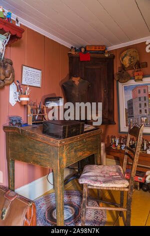 Antique wooden desk and chair in upstairs salmon coloured workroom with yellow painted wide plank floorboards inside an old 1835 Canadiana house - Stock Photo