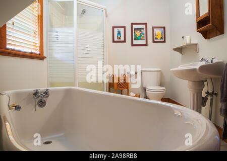 White claw foot bathtub, pedestal wash sink ,toilet and glass shower stall in en suite on upstairs floor inside a 1990s contemporary Victorian home - Stock Photo