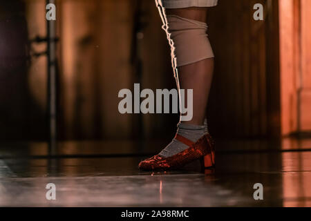 Side view of a person wearing red shiny women shoes and grey socks while standing on a stage - Stock Photo