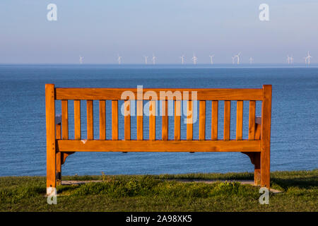 View of an empty bench and offshore Wind Farm from the coastal town of Tankerton in Kent, UK. - Stock Photo