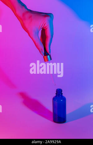 Bottle of blue on a neon trend background. Female hand holds a glass dropper. Gradient from pink to blue. Two shadows of different colors. - Stock Photo