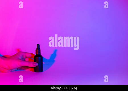 Female hand holds a bottle of black matte color on a neon trend background. Cosmetics concept. glass bottle mockup. - Stock Photo