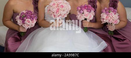 A bride with her bridesmaids all holding their bouquets and posing prior to the wedding ceremony - Stock Photo