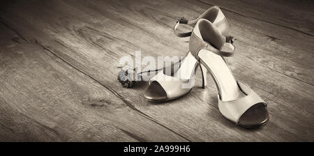 Argentine tango shoes with dry rose on wooden floor. Panoramic toned close-up image of pair of female dancing shoes. Sepia toned image with copy-space - Stock Photo