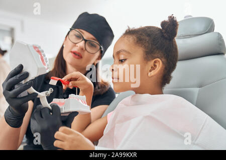 Female dentist in medical uniform and black hat, glasses and rubber gloves holding teeth model. Doctor teaching little patient how to brush teeth. African girl sitting and holding toothbrush.
