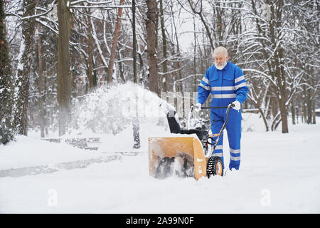 Janitor cleaning snow from walkway in park with snowblower. Elderly cleaner wearing in blue work overalls with safety band. Handsome man working in city service. - Stock Photo