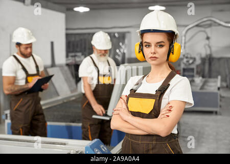 Beautiful female engineer looking at camera and posing during working day on metal factory. Young woman in helmet an uniform working with men and manufacturing products. Concept of metalwork. - Stock Photo