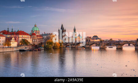 Prague, Czech Republic. Panoramic cityscape image of famous Charles Bridge in Prague during beautiful autumn sunset. - Stock Photo