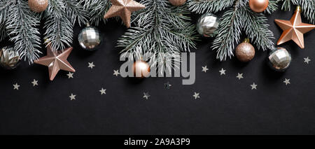 Christmas banner. Xmas frame top border made of pine tree branches decorated cooper and silver balls, stars, confetti. Flat lay, top view, copy space - Stock Photo