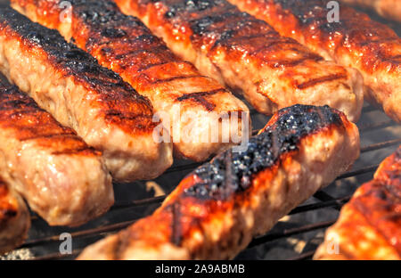 Grilling fresh meat on barbecue close up view - Stock Photo