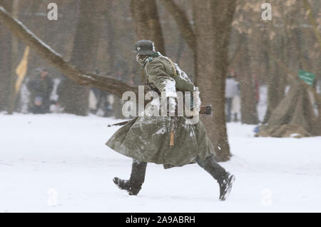 St. Petersburg (Russia) - February 23, 2017: Military historical reconstruction of events of World War II. Running german Wehrmacht soldier with a rif - Stock Photo