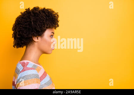 Profile photo of amazing dark skin lady looking seriously empty space not smiling wear casual striped t-shirt isolated bright yellow background - Stock Photo