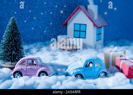 Small blue pink toy cars stand outdoors on snowy weather with red yellow giftboxes green pine tree white joyful family celebrate christmas eve in - Stock Photo
