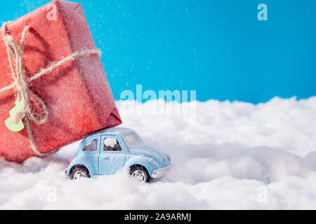 Little toy santa claus car carrying big red gift box on roof drive christmas jolly x-mas party under north-pole nature scene blue sky background - Stock Photo