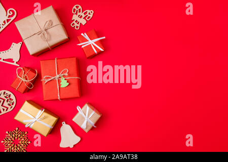 Photo of creative conept of presents wrapped among new year items like bells skates and snowflakes near copyspace isolated vibrant color red - Stock Photo
