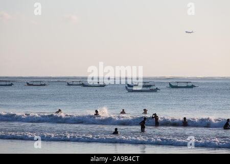 KUTA, INDONESIA. a group of people enjoying the sea wave, in the background there are fishing boat and aeroplane heading towards the local airport. - Stock Photo
