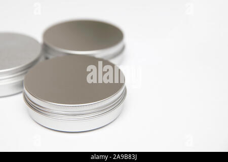 Lip balm in the round metallic tins isolated on the white background - Stock Photo