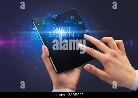 Businessman holding a foldable smartphone with SMART SECURITY inscription, cyber security concept
