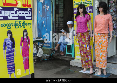 09.11.2015, Yangon , , Myanmar - A Muslim man sits next to mannequins from a women's fashion store and reads. 0SL151109D003CARO.JPG [MODEL RELEASE: NO - Stock Photo