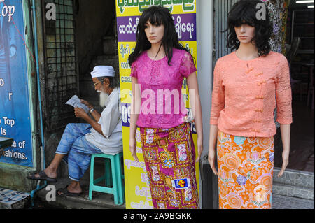 09.11.2015, Yangon , , Myanmar - A Muslim man sits next to mannequins from a women's fashion store and reads. 0SL151109D002CARO.JPG [MODEL RELEASE: NO - Stock Photo