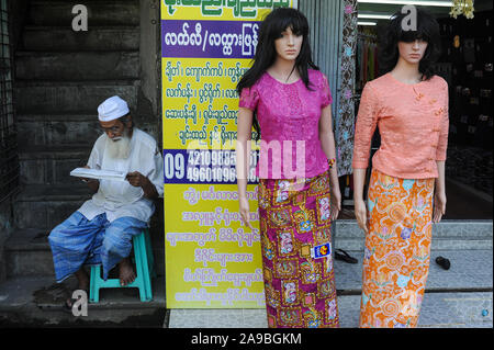 09.11.2015, Yangon , , Myanmar - A Muslim man sits next to mannequins from a women's fashion store and reads. 0SL151109D004CARO.JPG [MODEL RELEASE: NO - Stock Photo