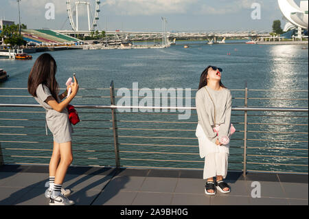 19.07.2019, Singapore, , Singapore - Tourists posing on the banks of the Singapore River in Marina Bay for photos with the ArtScience Museum in the ba