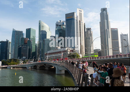 19.07.2019, Singapore, , Singapore - Visitors at the Singapore River in Marina Bay with skyscrapers of the business district in the background. 0SL190