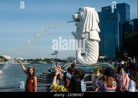 19.07.2019, Singapore, , Singapore - Tourists posing in Merlion Park on the banks of the Singapore River for photos with the business district in the