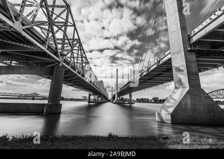 The Abraham Lincoln Bridge and John F. Kennedy Memorial Bridge crossing the Ohio River from Kentucky to Indiana. Long exposure sky and water movement. - Stock Photo