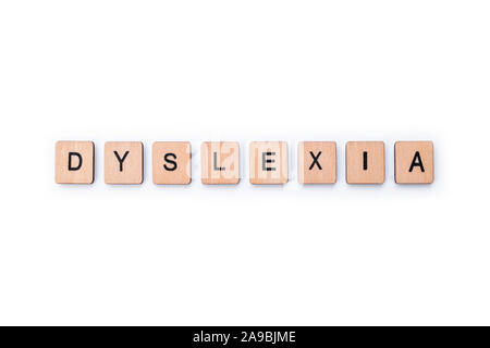 The word DYSLEXIA, spelt with wooden letter tiles over a white background.