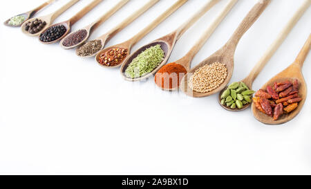Spices and wooden spoons against white background - Stock Photo
