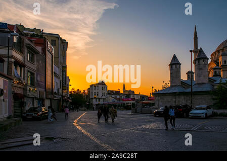 Street in Istanbul at sunsat, with buildings and mosque - Stock Photo