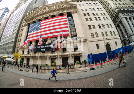 A giant American flag is unfurled across the facade of the New York Stock Exchange to commemorate Veterans Day in New York on Monday, November 11, 2019. Originally knows as Armistice Day, the holiday memorializes that on the eleventh hour of the eleventh day of the eleventh month the guns fell silent in1918 marking the end of World War I.  The holiday has since been expanded to include all American soldiers from all wars.(© Richard B. Levine) - Stock Photo