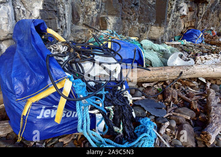 Beach tidy exercise cleaning up debris of ropes, plastic, wood washed up on a remote beach on the Isle of Mull in the Inner Hebrides of Scotland - Stock Photo