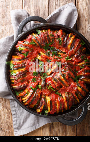 Vegetarian baked vegetable mix in tomato sauce close-up in a pan on the table. Vertical top view from above - Stock Photo