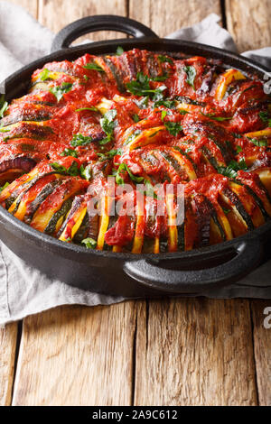 Vegetarian baked vegetable mix in tomato sauce close-up in a pan on the table. vertical - Stock Photo
